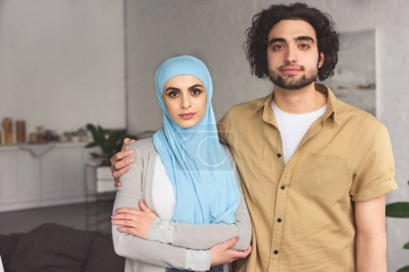affectionate muslim couple looking at camera at home