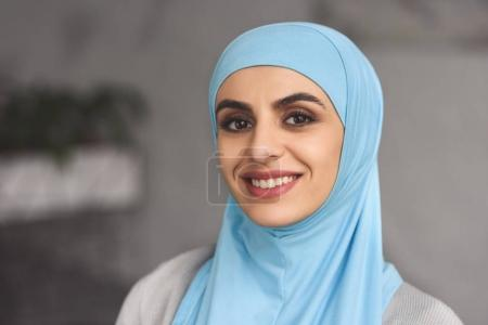portrait of smiling beautiful muslim woman in hijab at home