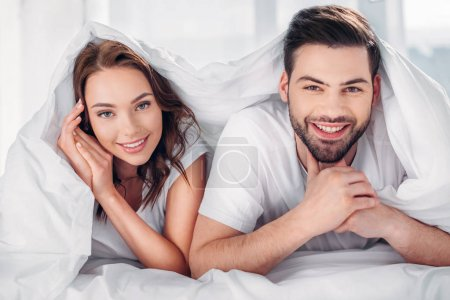 portrait of young happy couple covered with blanket looking at camera