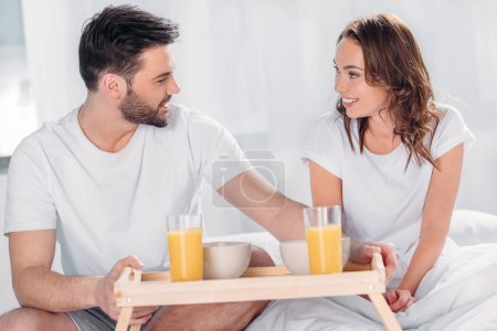 young man brought breakfast in bed for smiling girlfriend