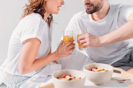 partial view of couple having breakfast in bed in morning together