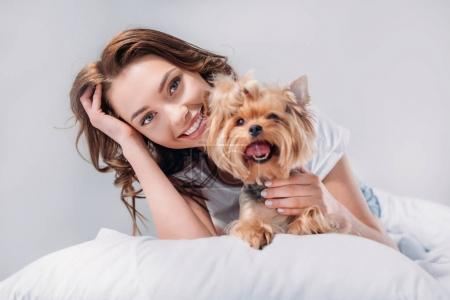 portrait of young smiling woman with yorkshire terrier resting on bed isolated on grey