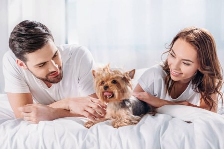 smiling couple in love with yorkshire terrier resting on bed together