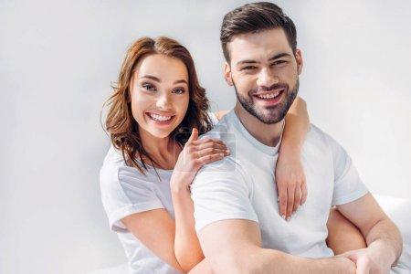 portrait of smiling pretty woman hugging boyfriend isolated on grey