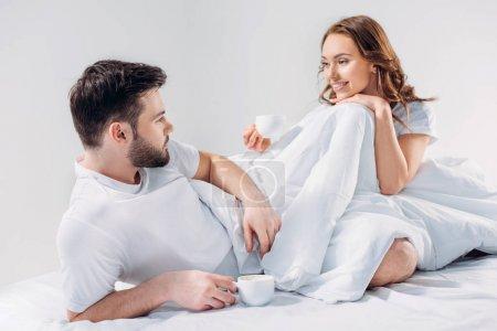 Photo pour Jeune couple avec des tasses de café au repos au lit ensemble isolé sur fond gris - image libre de droit