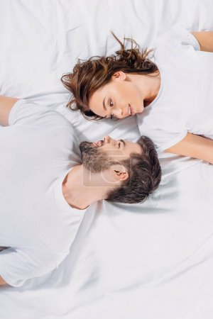overhead view of young couple in love looking at each other while lying on bed together
