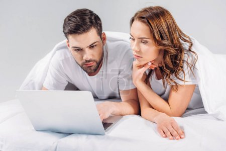 portrait of focused couple using laptop while resting on bed together isolated on grey