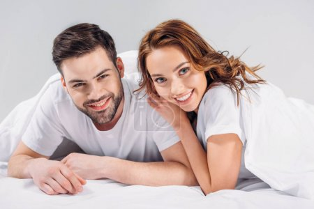 portrait of cheerful young couple in love looking at camera wile lying on bed together isolated on grey
