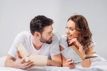 portrait of young smiling couple with books lying on bed isolated on grey