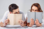 obscured view of young couple covering faces with books while lying on bed isolated on grey