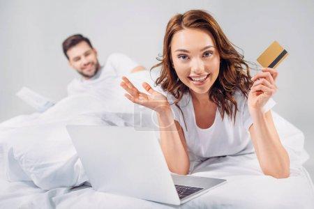 foyer sélectif de la femme souriante avec carte de crédit et ordinateur portable couché sur le lit avec petit ami isolé sur gris