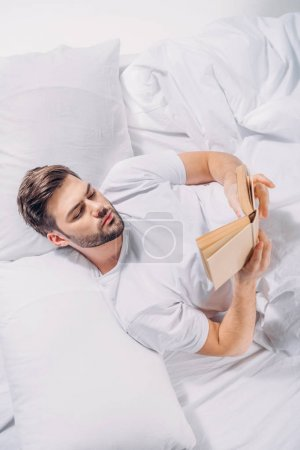 overhead view of focused young man reading book in bed
