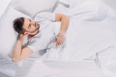 Photo pour Vue aérienne de l'homme barbu coûteux regardant loin tout en se reposant dans le lit - image libre de droit