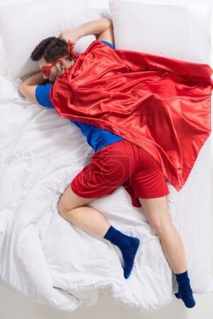 Photo pour Vue aérienne de l'homme en costume de super-héros dormant sur le lit - image libre de droit