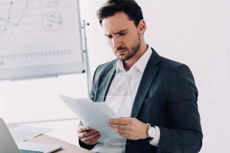 Photo for Serious handsome businessman reading documents in office - Royalty Free Image