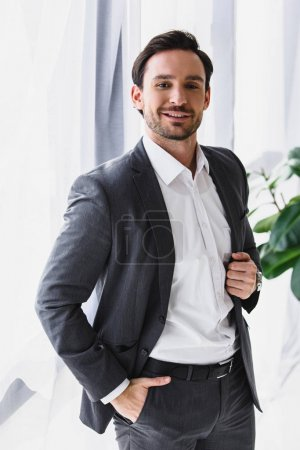 smiling handsome businessman looking at camera in office