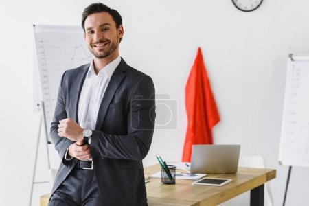 smiling super businessman standing near table and looking at camera in office