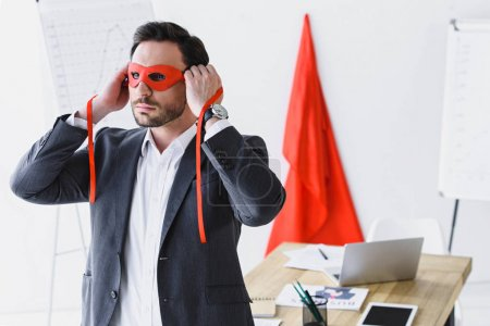 super businessman tying red mask in office