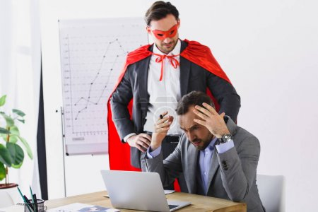 super businessman in mask and cape helping angry businessman with work in office