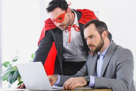 super businessman in mask and cape helping businessman with work in office