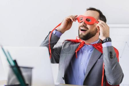 excited super businessman in cape looking through red mask in office