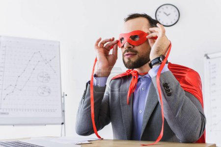 super businessman in cape looking through red mask in office