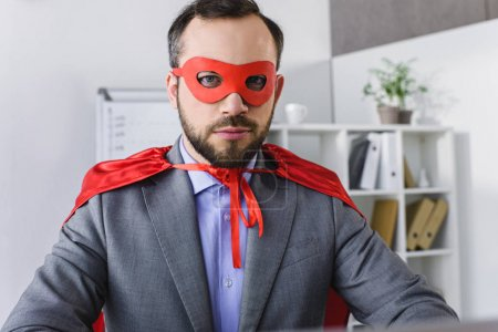 portrait of super businessman in mask and cape looking at camera in office
