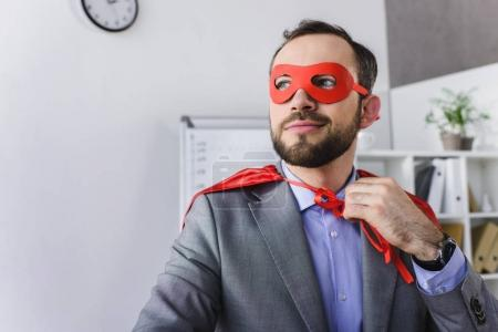 happy super businessman in mask and cape looking away in office