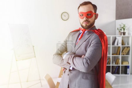 serious super businessman in mask and cape standing with crossed arms in office