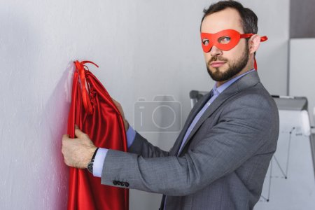 super businessman wearing mask and cape in office