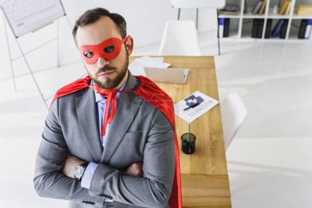 high angle view of super businessman in mask and cape looking at camera in office