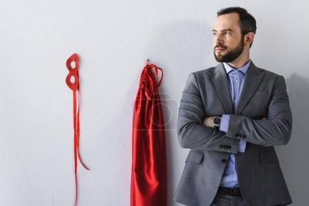 super businessman standing with crossed arms near mask and cape on wall in office