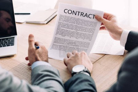 cropped image of businessman showing contract to colleague in office