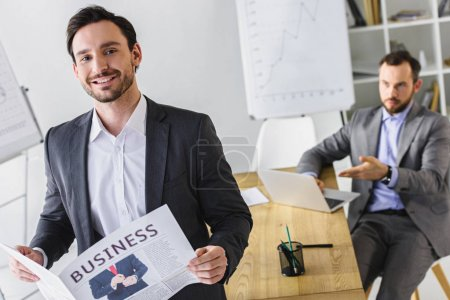handsome businessmen with newspaper and laptop in office