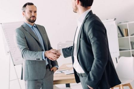 Photo for Handsome businessmen shaking hands in office - Royalty Free Image
