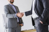 cropped image of businessmen shaking hands in office