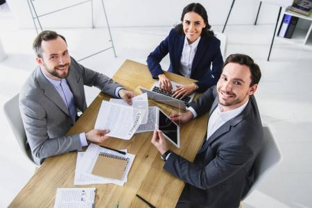 high angle view of smiling businesspeople working with gadgets in office