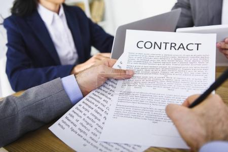 cropped image of businessman signing contract in office
