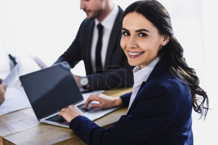 Photo for Smiling businesswoman working with laptop in office and looking at camera - Royalty Free Image