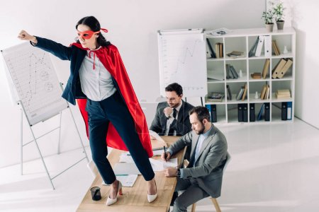 super businesswoman in mask and cape standing on table with hand up in office