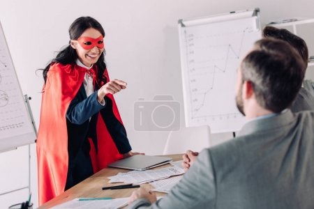 smiling super businesswoman in mask and cape pointing on businessmen in office