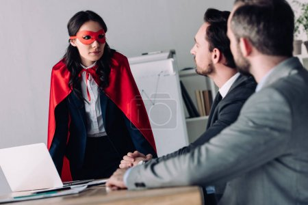 super businesswoman in mask and cape helping businessmen in office