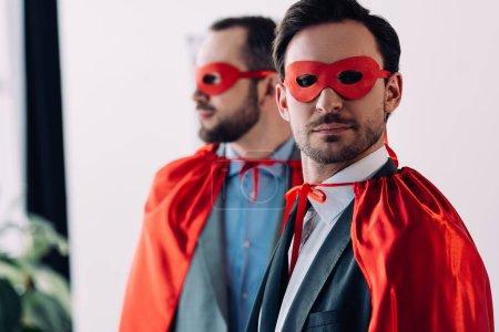 Portrait des hommes super beau masques et capes au bureau
