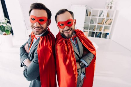 high angle view of smiling handsome super businessmen in masks and capes with crossed arms in office