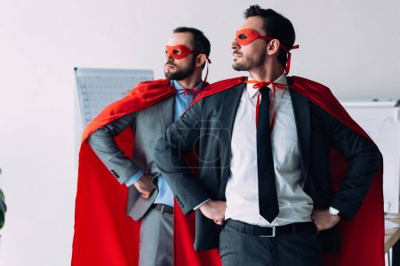 handsome super businessmen in masks and capes standing with hands akimbo in office