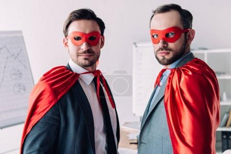 portrait of handsome super businessmen in masks and capes in office