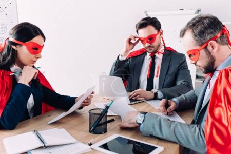 pensive super businesspeople in masks and capes working in office