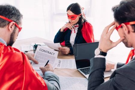 super businesspeople in masks and capes at brainstorm in office