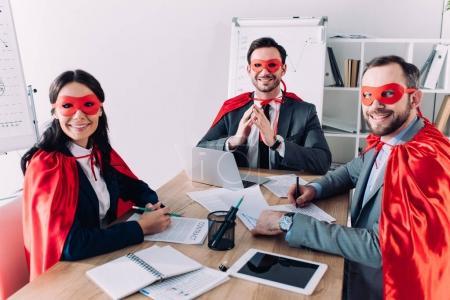 Photo pour Les gens d'affaires super souriants en masques et capes assis à table dans le Bureau - image libre de droit
