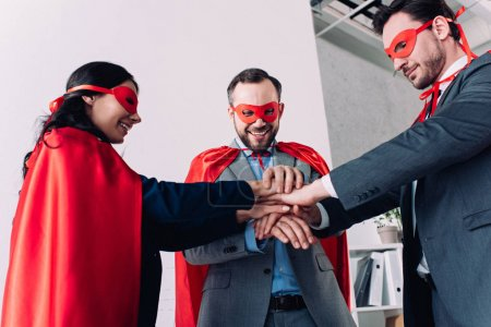happy super businesspeople in masks and capes putting hands together in office